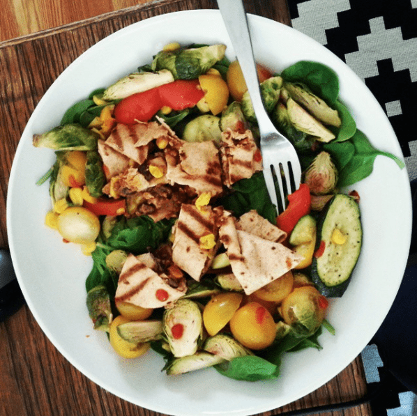 Photo of salad with grilled chicken in a white bowl