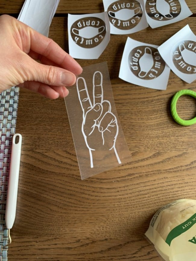 photo of Brittany Wells holding a decal of a hand making a peace sign with other craft materials and decals in the background