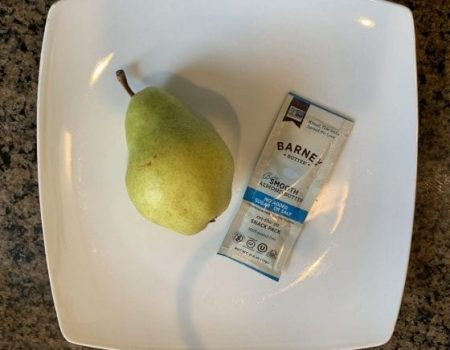 Photo of a pear and a packet of almond butter on a white plate